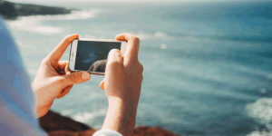 Person using cell phone at the beach, taking a picture of the ocean.